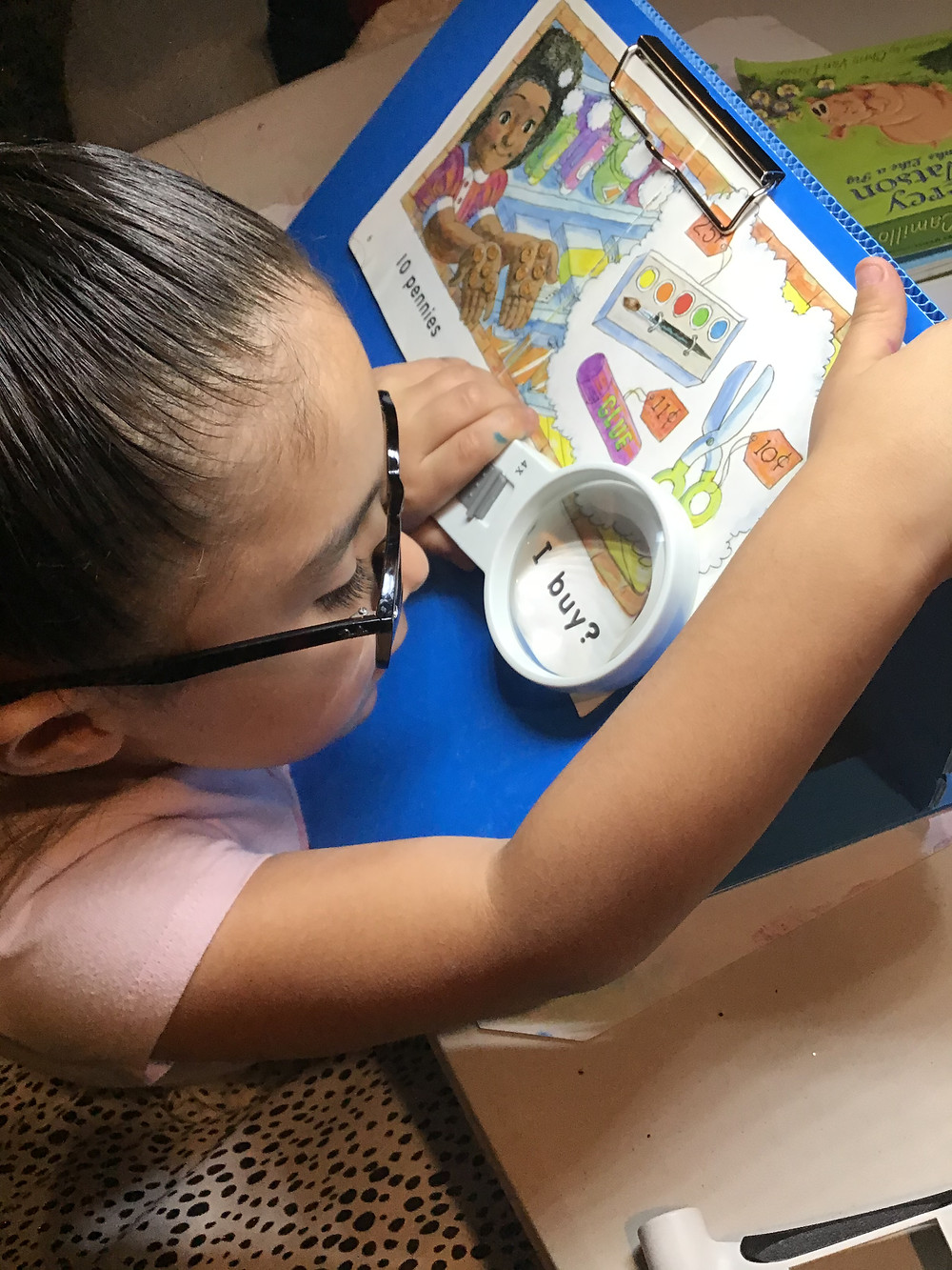 Aliyah reading thanks to 4x magnifier and slant board