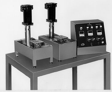 """(Below) This Selective Soldering System consists of a Model M3 Wave Solder Pot and  Model C3 Wave Fluxer. Both are equipped with a nozzle and fixture to solder a small electrical assembly. """"The operator first places the assembly on the fluxer and presses a foot pedal. A timer controls the flux flow to about one second. The assembly is next placed on the wave solder pot fixture and another foot pedal is activated. A timer controls the solder flow to about two seconds. The cycle is now complete and the assembly Is removed."""""""