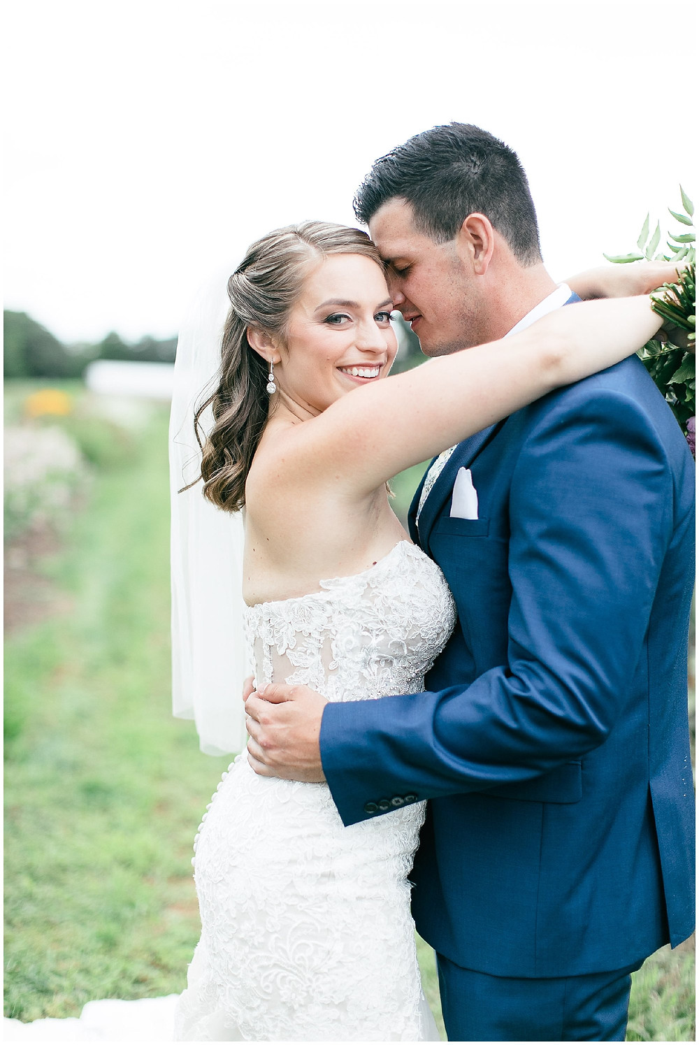 bride and groom portrait in a field of flowers makes for a romantic image