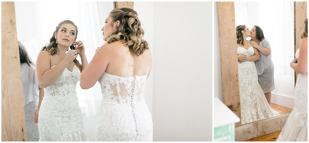 Bride wears her earrings while looking into the full body mirror. The mother of the Bride kisses her, moments captured through the reflection of the mirror.