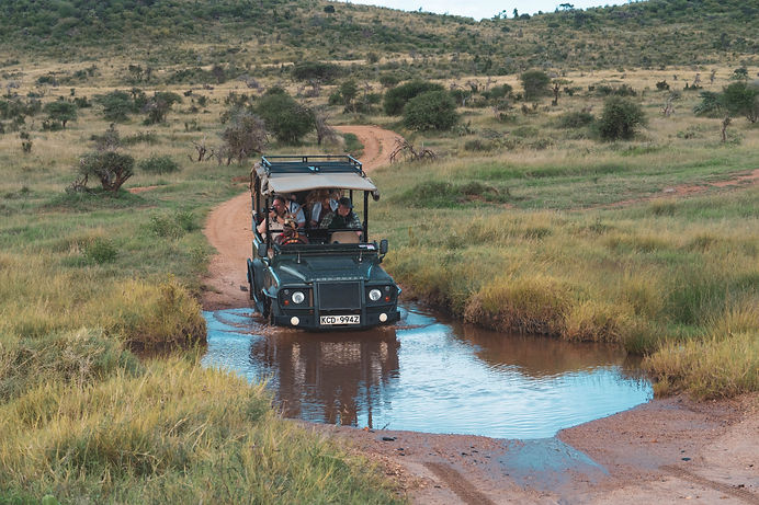 A group of people in a Land Rover, on safari in Africa, driving through a water hole in the bush, while taking photographs.