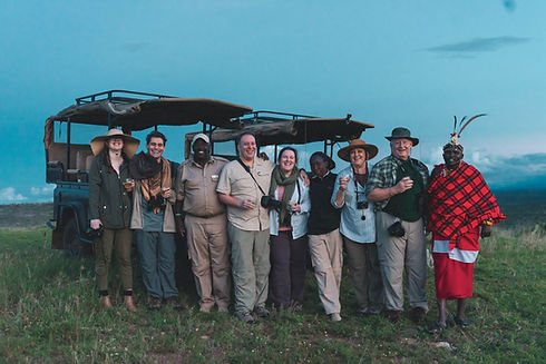 Six guests, two guides, and one tribesman posing for a photo in front of two safari vehicles in Kenya.