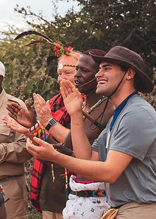 A male member of an African tribe clapping with two visiting men. One man is wearing a hat and the other is wearing some traditional garb from the tribe. The tribesman is wearing colorful bracelets and necklaces.
