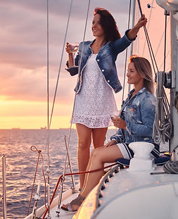 Two women relaxing on a yacht with drinks. They are wearing denim jackets over white dresses. It is dusk.