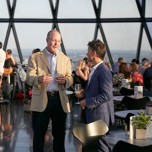 Two men standing in suit coats with glasses of wine, talking. Large windows behind them reveal that they are in a restaurant on top of a skyscraper.
