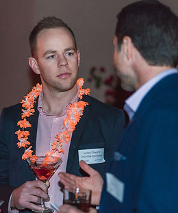 Two men in suit jackets, standing and talking while drinking cocktails. One man is wearing an orange and white lei.