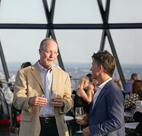 Two men in suit jackets, standing and talking while having drinks in a restaurant. Large windows behind them reveals that they are high in a skyscrapper and a cityscape is shown outside.