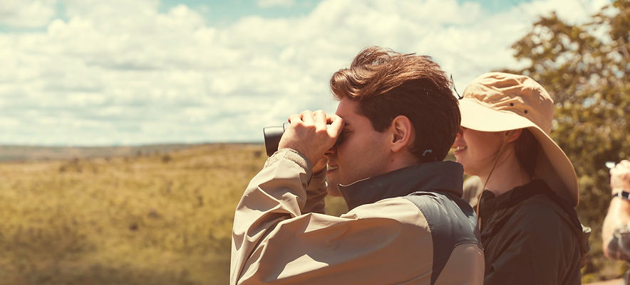 A man and woman on safari, looking over the African landscape through binoculars.