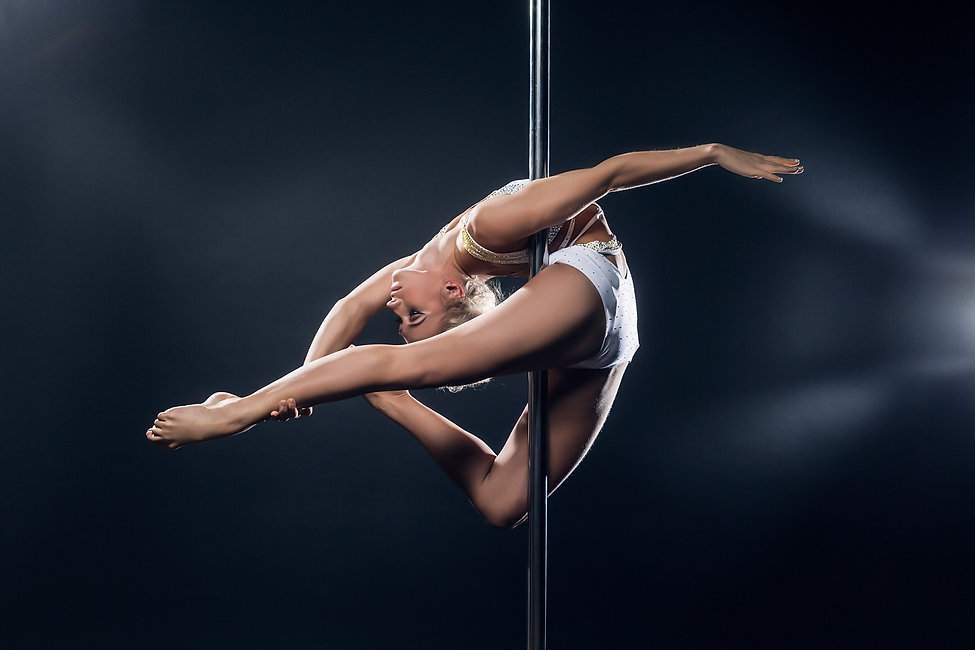 An incredible balletic and contortionist style advanced pole dance move with a beautiful pole dancer in a white costume performing an aerial arabesque move on the pole which consists of a backbend where she grabs her back leg while suspended on the pole.