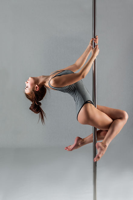 Athletic pole dancer in a grey leotard performing a beginner upright pole move known as a pole sit or a secretary sit with legs crossed on the pole.