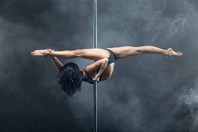 Stunning advanced pole dancers performing an advanced inverted split on the pole, known as a Machine Gun in pole dancing.