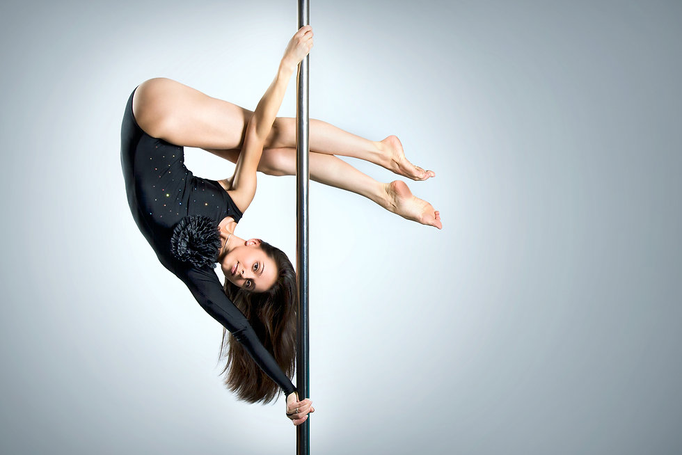 A female pole dancer with long dark hair in a dark blue leotard performing a move on the pole known as a Wedge. She is inverted in a split grip with her legs criss crossed over her head while suspended on the pole.