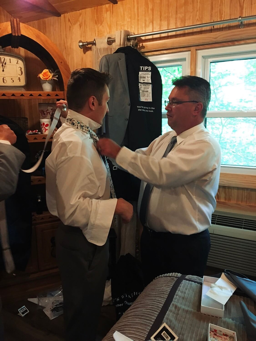 Father of the groom tying his son's tie before his wedding