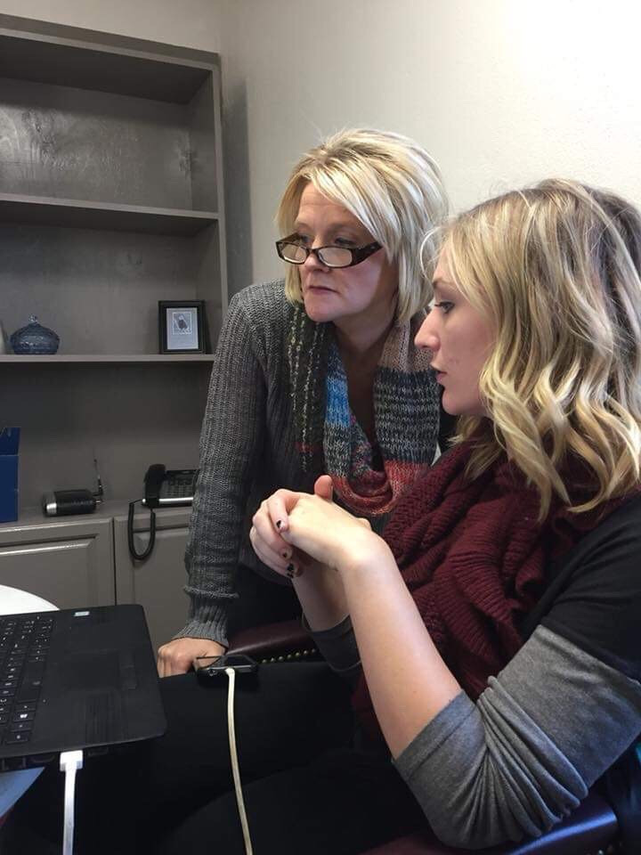 Mom and teen daughter working on computer together
