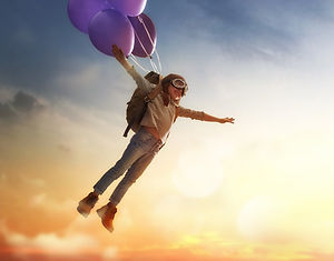 Dreams%20of%20travel!%20Child%20flying%20on%20balloons%20against%20the%20backdrop%20of%20a%20sunset.