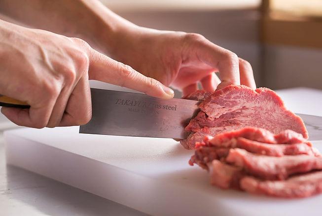 包丁でカットされるお肉