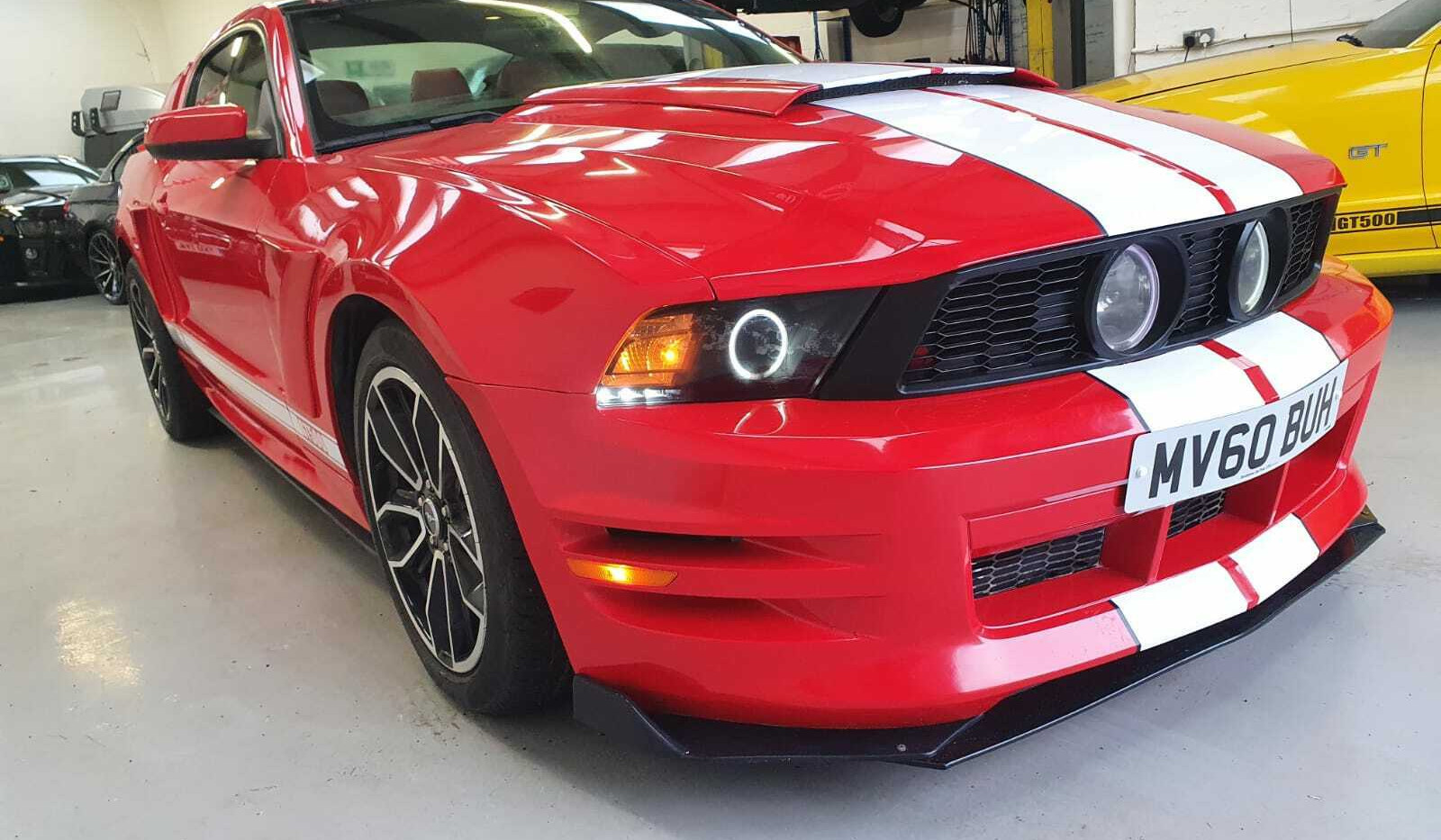 """2010 FORD MUSTANG GT500 - £18,495  V8 Facelift, fresh import!  - Automatic - 5.0 L - Coupe - Petrol - 2 Doors - 4 Seats  Amazing looking, sounding, and driving sports coupe.  5.0 GT V8 powertrain, 412 bhp sounds wonderful, glass panoramic roof, twin sports exhaust, cold air induction kit, upgraded headlamps, 19"""" wheels  Full GT bodykit and GT500 body stripes in Atlantic White  Finished in torch red with matching brick-read leather interior/ivory stripe inserts"""