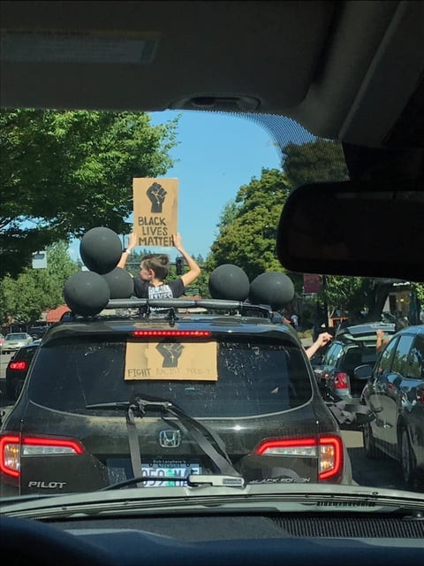 Youth holds a Black Lives Matter sign through a car's sun roof.