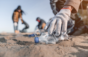 People collecting plastic litter from a beach