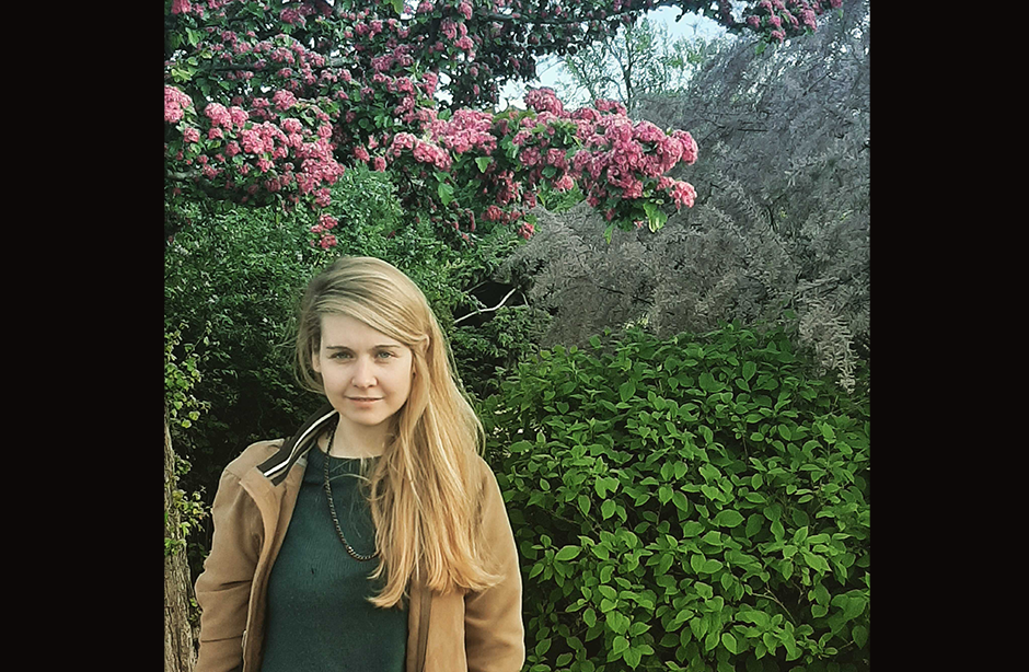 Young woman smiling at the camera, standing in front of bushes