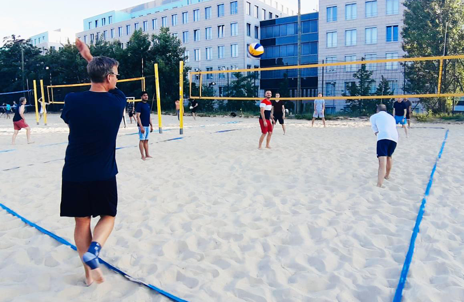 4 men playing beach vollyeball
