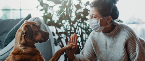 Woman in mask giving her dog a high-five