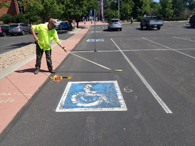 A technician stands to the left of an accessible parking space and pushes out a tape measure across its width.