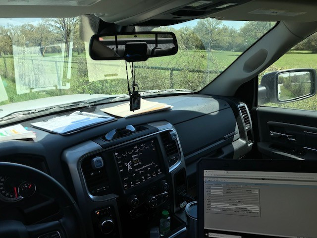 Picture taken from perspective of driver in a truck looking at an open laptop sitting on the truck console.