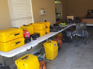 In a garage, a table is piled high with yellow boxes that contain field equipment.