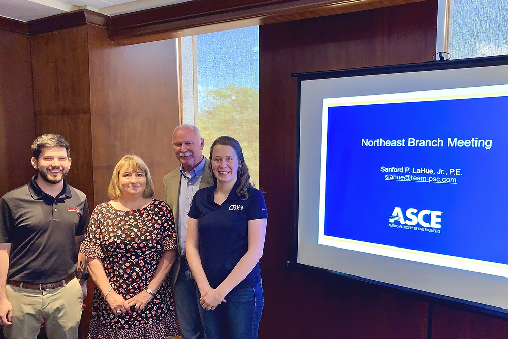 "A group of four ASCE officers stand to the left of a projector screen that reads ""Northeast Branch Meeting ASCE."""