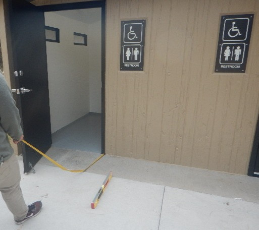 A man holds a measuring tape leading to the doorframe of an outdoor accessible public restroom.