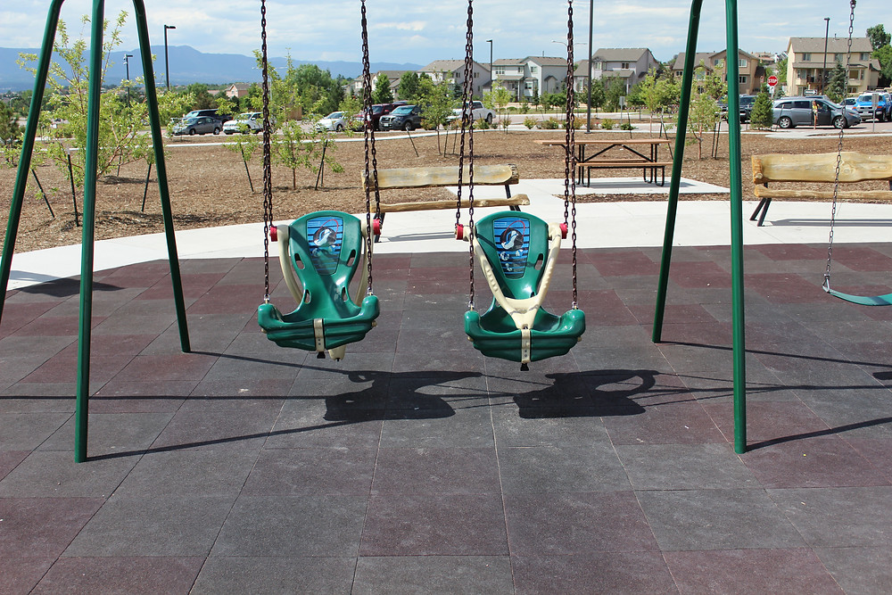 Two swings with safety harnesses hang over a flat, rubber playground surface designed for wheelchair access.
