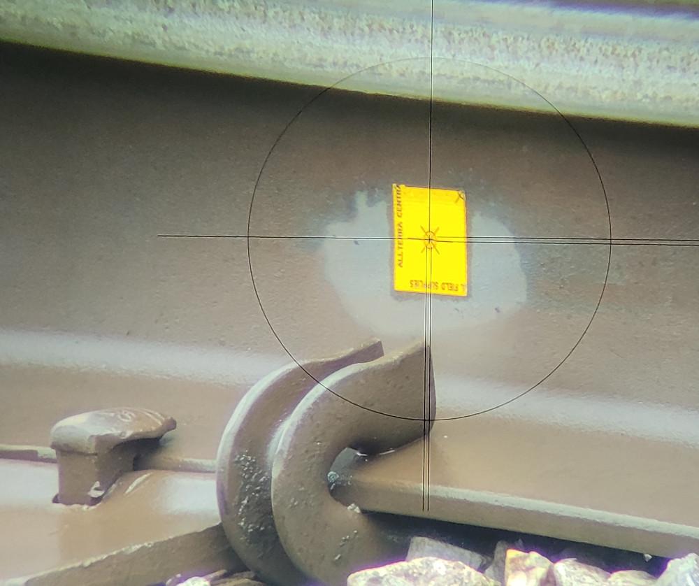 Adhesive target sticker on rail seen through Trimble in crosshairs.