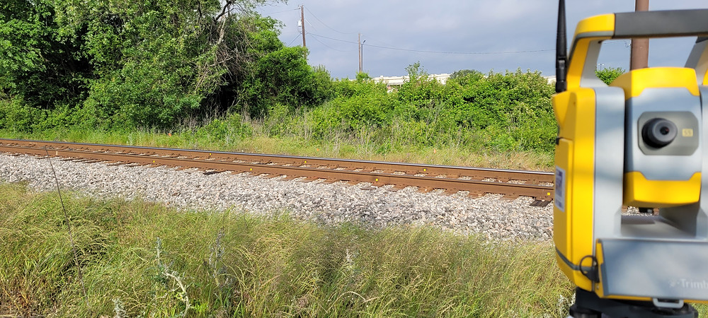 Trimble equipment in the foreground pointing towards railroad in the background.
