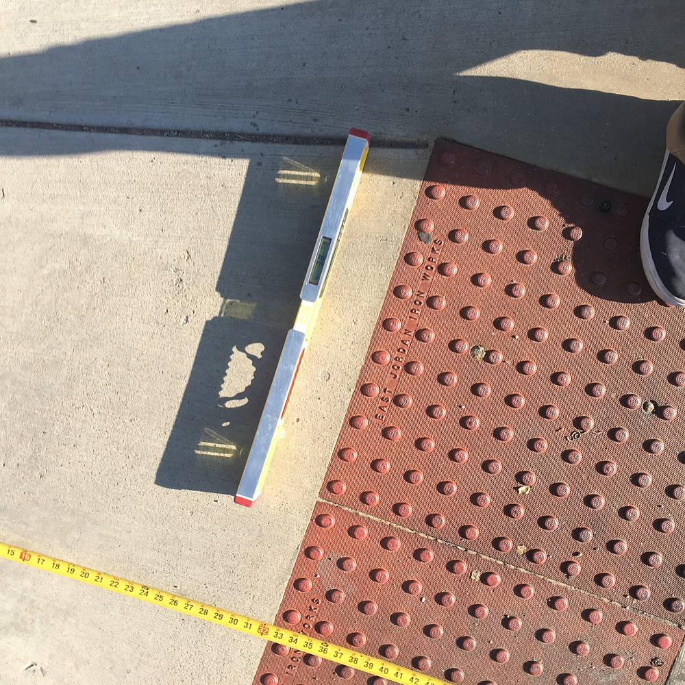 A Smart Level and tape measure confirms accessible slope of a sidewalk ramp.