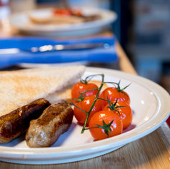 Homemade vegan English-style sausages and roasted cherry tomatoes