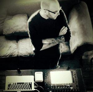 Man with crossed arms standing in front of a computer.