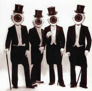 Four figures with eyeballs for heads  wearing tuxedos.