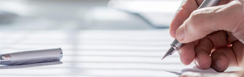 une personne qui ecrit avec un stylo