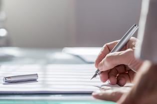 יד אוחזת בעט לקראת חתימה על מסמך