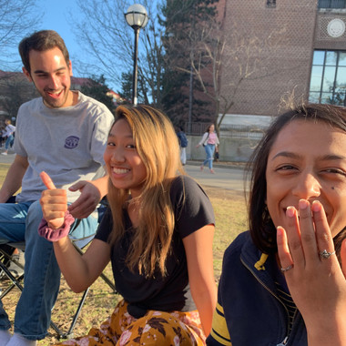 Scott McMillan, Kelly Chang, and Anjali Nemorin pose for a photo on a beautiful day in the Diag