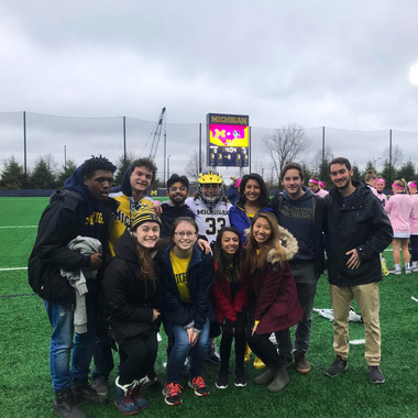 Greenies take a group picture right before singing the national anthem at a Women's Lacrosse game against Johns Hopkins (Winter 2019)