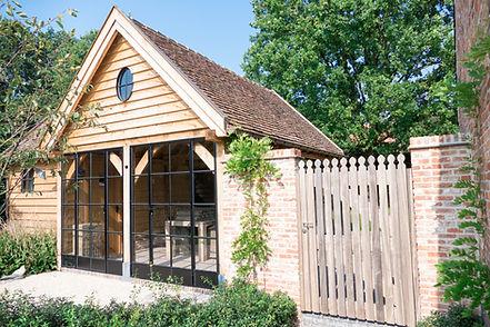 Poolhouse en overdekt terras met zwart gepoederlakte metalen ramen, eiken bijgebouw