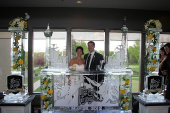 8ft Ice Bar and ice pillars on each side - features drink luge runs on each side of bar and flowers were frozen into the pillars and columns in the bar.  Colored sand was also used to highlight names and the couple's monogram.