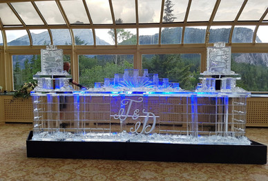 16ft Ice Bar - featuring a brickwork design with initials engraved in the centre.  There is a bottle holder that sits in the centre top of the bar and drink luge runs on each side.