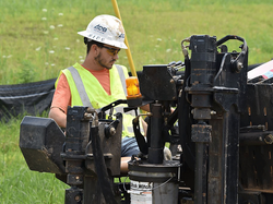 An ADB employee examines a DitchWitch ma