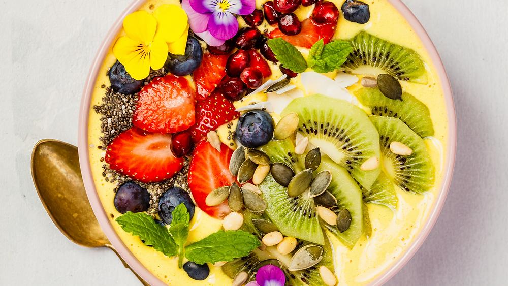 Smoothie bowl su base gialla, ricca di frutta colori e dettagli. immagine presa dal web