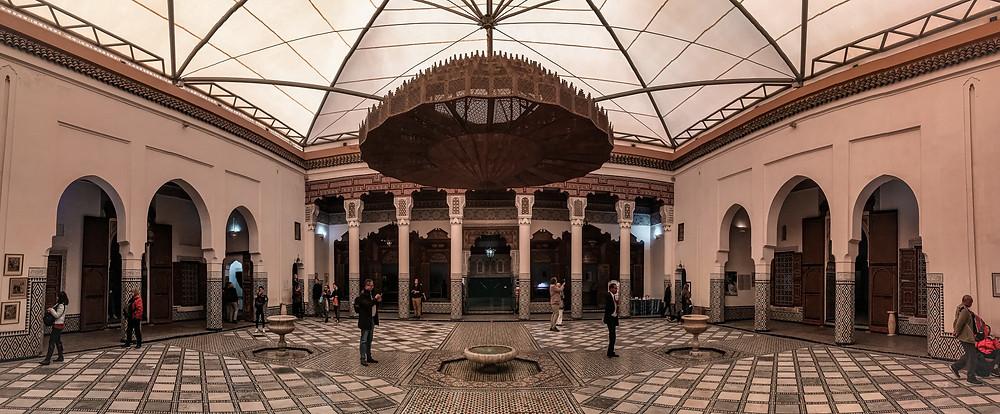 Sala del Museo di Marrakech. Enorme lampadario in posizione centrale, pavimento e colonne in secondo piano adornate e decorate in tipico stile marocchino.