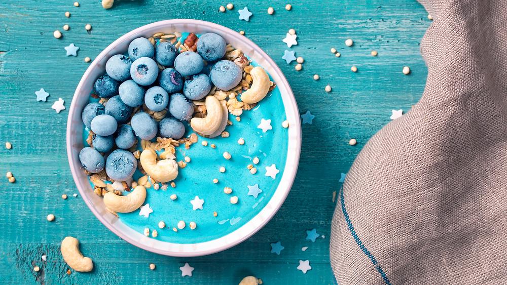 Bowl di frutta dai colori accesi sui toni dell'azzurro. Frutta fresca e frutta secca al centro dell'immagine. Fotografia presa dal web