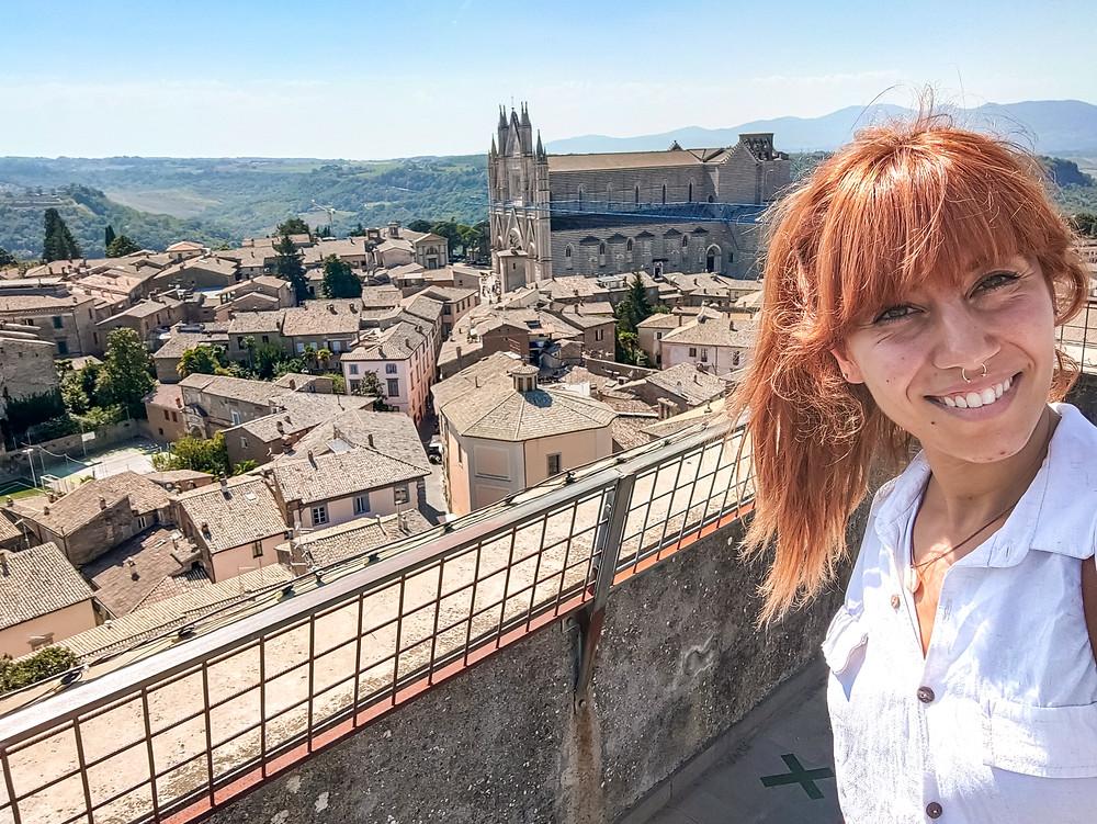 Eccomi in un autoscatto in cima a Torre del Moro. Oltre ai tetti delle case, è possibile vedere il duomo ed i campi oltre alla città di Orvieto.